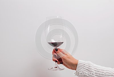 Woman`s hand in a white sweater holding a glass of red wine.