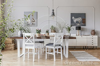 Real photo of a rustical dining room interior with a wooden table, chairs and plants