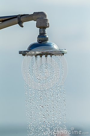 Mage of a vintage old shower head splashing water close up background. Water flows from the head of an old shower. Background for