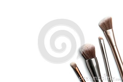 Four shiny bronze- and silver-coloured makeup brushes for applying powder, eyeshadow, eyeliner, bronzer and highlighter arranged