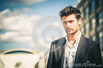 Man in suit and white shirt looking. Outdoors on the street in the city