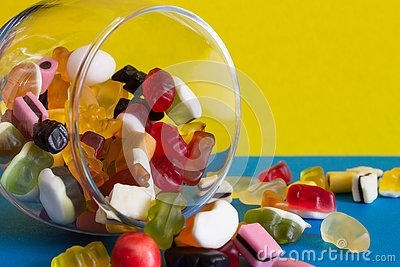 stock image of colorful candies in jar on blue background