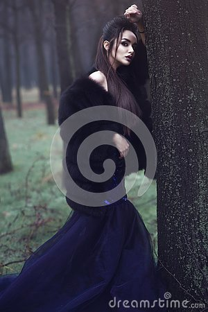 Beautiful lady in luxurious sequin evening dress and sable fur coat standing in the mysterious misty woods