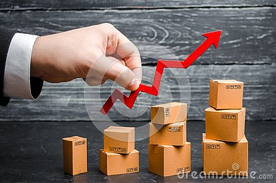 A businessman`s hand holds a red arrow up above cardboard boxes folded incrementally. Sales growth and increase in exports