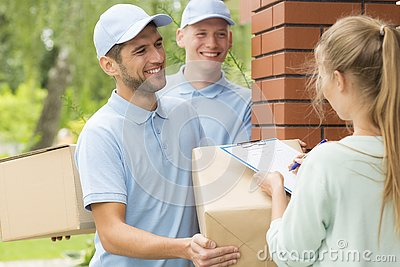Smiling couriers in blue uniforms and young women filling up delivery documents