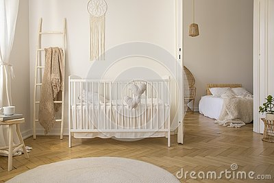 Wooden ladder with beige blanket white crib real photo