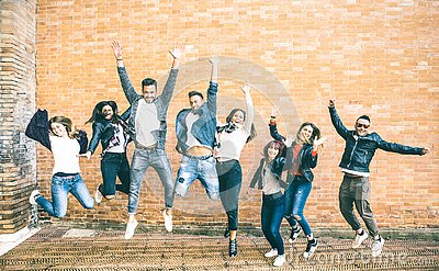 Happy friends millennials jumping and cheering against brick wall