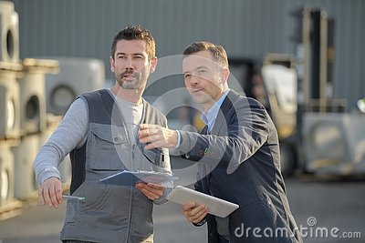Manager with worker discussing over clipboard in industry