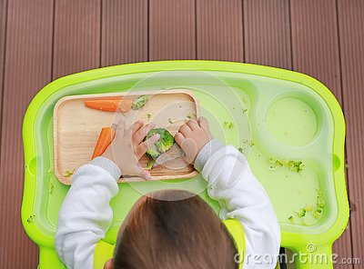 Top view of infant baby eating by Baby Led Weaning BLW. Finger foods concept