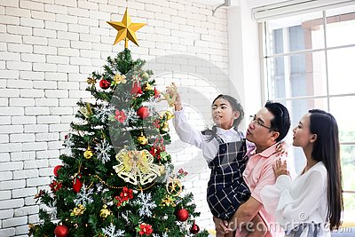 Family decorating a Christmas tree and Father giving Christmas G