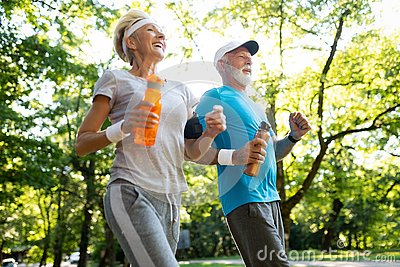 stock image of fitness, sport, people, exercising and lifestyle concept - senior couple running