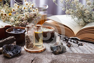 Authentic interior details, glass of herbal rea, homeopathic treatment on rustic wooden background top view, alternative medicine