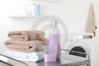 Stack of clean towels and detergent on table