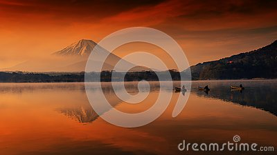 Silhouette view of fishermen on boats with mist and twilight sky during dawn at Shoji lake in Yamanashi, Japan. Landscape with