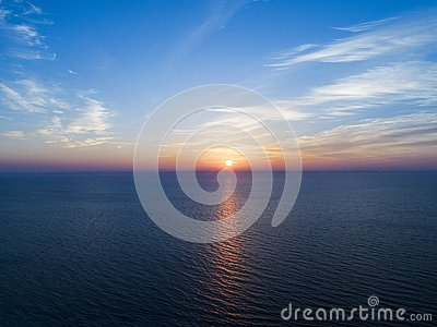 Aerial view of a Sunset sky background. Aerial Dramatic gold sunset sky with evening sky clouds over the sea. Stunning sky clouds