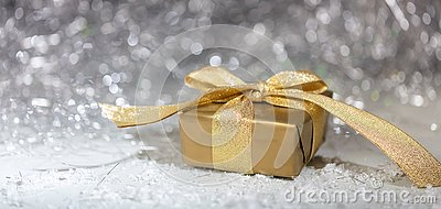 Christmas golden gift box on abstract bokeh lights and glitter background