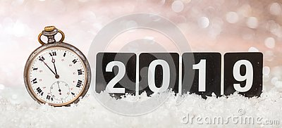 2019 New Years eve celebration. Minutes to midnight on an old watch, bokeh festive background