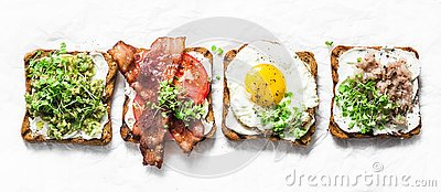 Variety of sandwiches for breakfast, snack, appetizers - avocado puree, fried egg, tomatoes, bacon, cheese, smoked mackerel