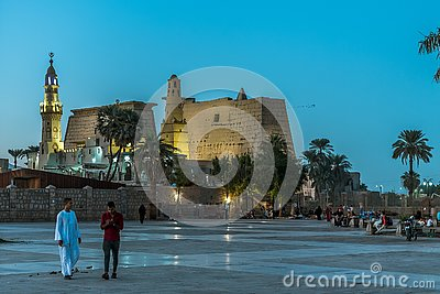People walking in the square in front of the ancient illuminated Luxor temple at night with dark blue sky and glowing brickwalls