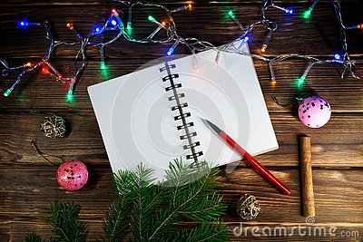 Template letters with New Year and Christmas greetings or a list of gifts. Opened notebook is located at an angle. Happy New Year