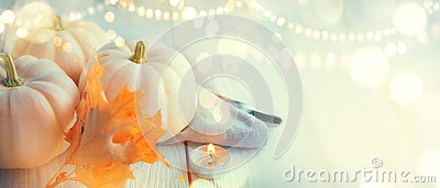 Thanksgiving background. Wooden table, decorated with pumpkins, autumn leaves and candles