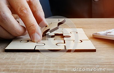 Business success and problem solving. Man holds piece of puzzle