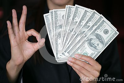 Business woman displaying a spread of cash over, spending money or profit from business operations concept