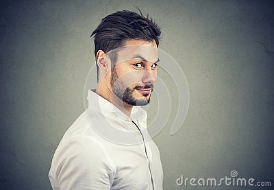 Dishonest man in white shirt looking with pretend smile at camera on gray background