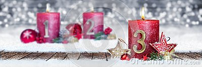 third sunday of advent red candle with golden metal number one on wooden planks in snow front of silver bokeh background