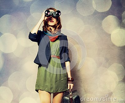 Style redhead girl with binocular and suitcase