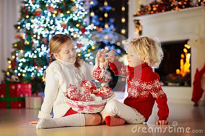 Child decorating Christmas tree at home. Little boy and girl in knitted sweater with handmade Xmas ornament. Family celebrating
