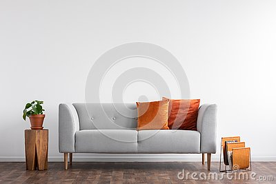 Comfortable couch with orange and red pillow in spacious living room interior,