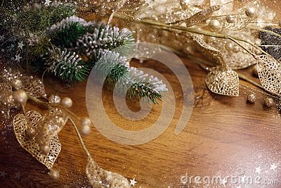 Christmas background with pine branches shiny golden decor and New Year`s tinsel blazes bokeh