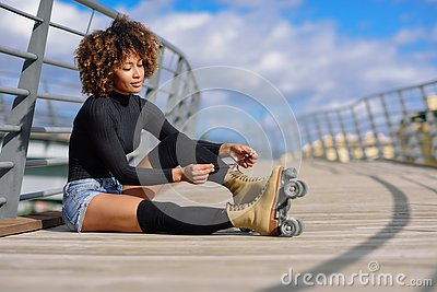 Young black girl sitting on urban bridge and puts on skates. Woman with afro hairstyle rollerblading on sunny day