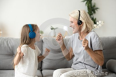 Happy grandmother and granddaughter listening to music in headph