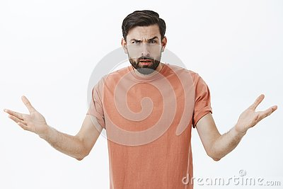 stock image of confused and annoyed angry bearded boyfriend cannot understand why arguing, frowning with clueless emotions shrugging