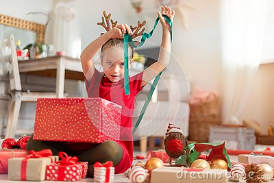 Cute young girl opening large red christmas present while sitting on living room floor. Candid family christmas time.