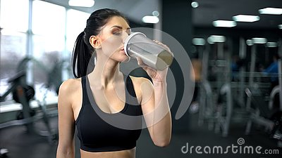 Sporty woman drinking protein shake after workout, muscle gain nutrition, health