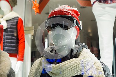 Male mannequin in store window during winter with ski gear, woolly hat, dark goggles, scarf, down jacket and fake snow on head