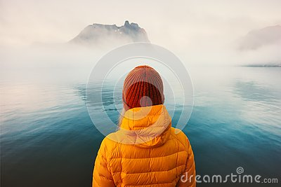 Woman alone looking at foggy cold sea traveling adventure lifestyle