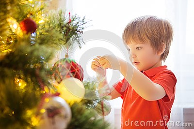 Xmas party celebration. Child decorating Christmas tree at home. Family with kids celebrate winter holidays. New year small boy at