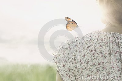 A colorful butterfly leans delicately on the shoulders of a girl
