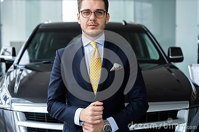 Confident in his choice. Mature grey hair man in formalwear standing in front of car and looking at camera.