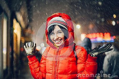 Happy exited woman having fun on city street of New York under the snow at winter time wearing hat and jacket