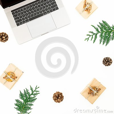 Laptop with Christmas gifts, evergreen branches and pine cones on white background. Holiday office composition. Top view. Flat lay