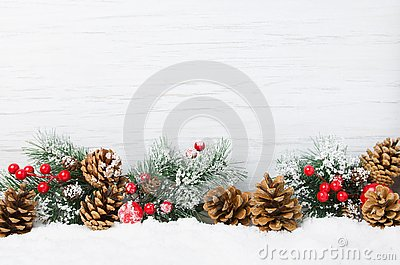 Christmas snow scene. Christmas tree branches with cones and ornaments on wooden light background,