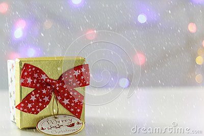 Gift box with red bow and defocused christmas lights on the background. With snow effect