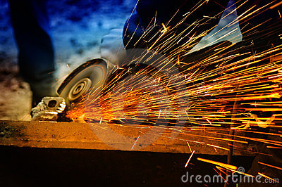 Worker grinding/welding metal and sparks spreadi