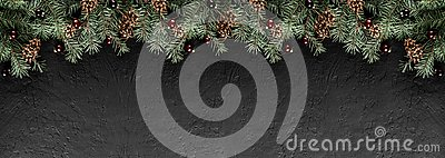 Christmas Fir branches with pine cones on dark black background. Xmas and Happy New Year card, bokeh, sparking, glowing.