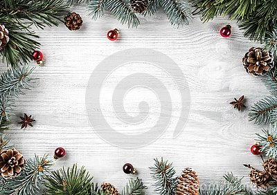 Creative frame made of Christmas fir branches on white wooden background with red decoration, pine cones. Xmas and New Year theme